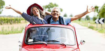 Retired Man and Woman waving goodbye in red car
